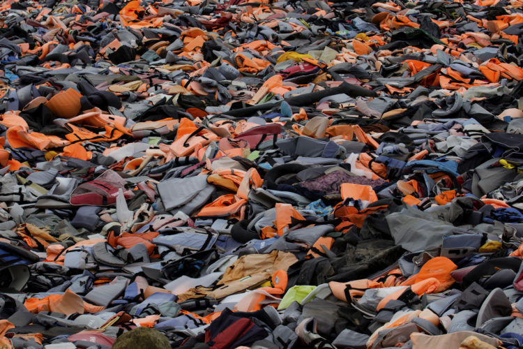 """LESVOS, GREECE (EU) 06-04-2017: The """"Lifejacket Graveyard,"""" a dumping ground for thousands of discarded life jackets and rubber rafts used by refugees and their smugglers to get to Lesvos, Greece, has become a symbol of the thousands of refugees who have sought asylum in Greece (EU), including many who drowned."""