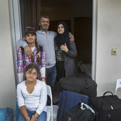 """ATHENS, GREECE (EU) 05-29-2017: The Al Rahmoun family arrive at their new apartment in Athens after living in a refugee squat in an abandoned school building for the past few months. They are being sponsored by two sisters in New York who raised money for them through HumanWire's Tent-to-Home Project, the new apartment is a welcome relief from the refugee camps they had been living in, one with conditions so dire that the mother, Manar, had resorted to sucking on the ears and faces of her children to keep them clean. They found the new apartment so blessed, it was """"like a wedding feeling,"""" Hosam said, a place where their children liked sitting in the bathtub. The Al Rahmoun's fled the war in Syria and have been refugees for over a year, and are now awaiting a ruling on their asylum application in Greece (EU)."""