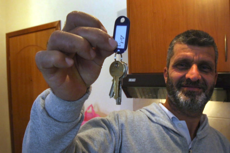 ATHENS, GREECE (EU) 05-29-2017: Hosem Al Rahmoun proudly holds-up the keys to his family's new apartment after living huddled in a refugee squat in an abandoned school building in Athens for the past few months. They are being sponsored by two sisters in New York who raised money for them through HumanWire's Tent-to-Home Project, the new apartment is a welcome relief from the refugee camps.