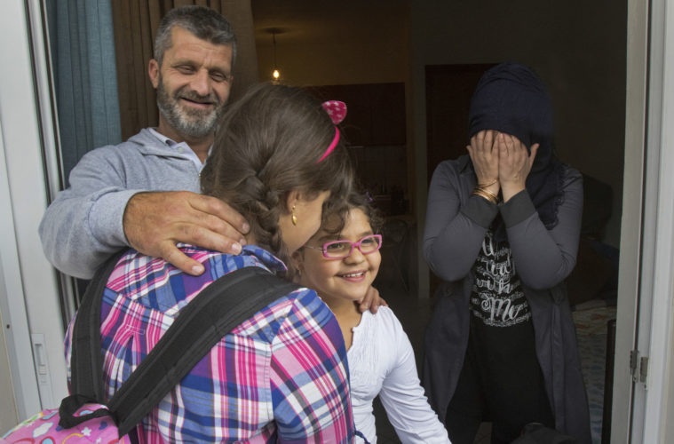 ATHENS, GREECE (EU) 05-29-2017: Hosem and Manar Al Rahmoun share a happy moment with daughters Sara and Hala in their new apartment in Athens after living in a refugee squat in an abandoned school building for the past few months. They are being sponsored by two sisters in New York who raised money for them through HumanWire's Tent-to-Home Project, the new apartment is a welcome relief from the refugee camps. The family was giddy over their good fortune.