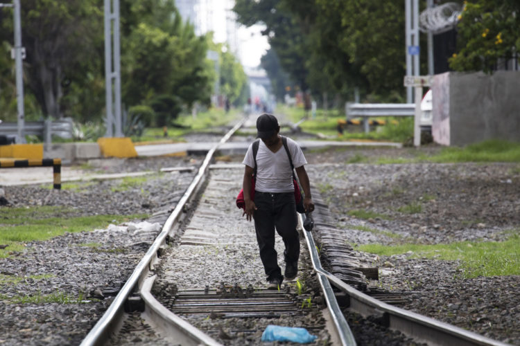 GUADALAJARA, MEXICO  07/14/2017: A migrant walks along the railroad tracks in Guadalajara where the Mexican freight train known as La Bestia (the Beast) that is utilized by U.S. bound migrants on their journey to the United States to more quickly traverse the length of Mexico. This mode of travel is extremely dangerous and illegal. Guadalajara, roughly the midway between Central American and the U.S. border.  According to the Migration Policy Institute (MPI), a half a million Central American immigrants ride atop La Bestia during their long and perilous journey through Mexico to the U.S. The migrants often must latch onto the moving freights, which run along multiple lines, carry products north for export, and must ride atop the moving trains, facing physical dangers that range from amputation to death if they fall or are pushed. Beyond the dangers of the trains themselves, Central American migrants are subject to extortion and violence at the hands of the gangs and organized-crime groups that control the routes north.