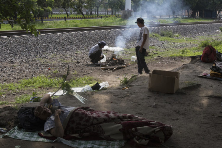 GUADALAJARA, MEXICO  07/14/2017: A group of Honduran migrants make camp along the railroad tracks in Guadalajara, roughly the midway between Central American and the U.S., along the route of Mexican freight trains that are utilized by U.S.- bound migrants to more quickly traverse the length of Mexico, also known as La Bestia and El tren de los desconocidos. This mode of travel is extremely dangerous and illegal.  According to the Migration Policy Institute (MPI), a half a million Central American immigrants ride atop La Bestia during their long and perilous journey through Mexico to the U.S. The migrants often must latch onto the moving freights, which run along multiple lines, carry products north for export, and must ride atop the moving trains, facing physical dangers that range from amputation to death if they fall or are pushed. Beyond the dangers of the trains themselves, Central American migrants are subject to extortion and violence at the hands of the gangs and organized-crime groups that control the routes north.