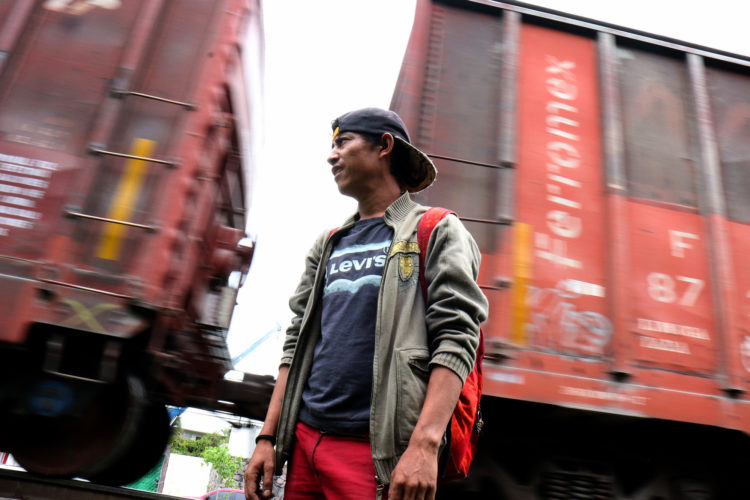"""GUADALAJARA, MEXICO  07/11/2017: Enrique, a migrant from Honduras, waits for the right moment to jump aboard a moving freight train, known as La Bestia, in Guadalajara. Migrants use the freight trains on their journey to the United States to more quickly traverse the length of Mexico. This mode of travel is extremely dangerous and illegal. Guadalajara, roughly the midway between Central American and the U.S. border. Enrique says this this his 4th attempt to make it into the U.S., previous attempts resulted in being deported back to Honduras. If he makes it across, he plans to look for his a half-sister living in Trenton, NJ.The journey to the United States is often long and involves several steps. Before migrants can get on the train they must travel from their homes through Central America to the Mexican border. Crossing the border is relatively easy as, even with increased surveillance, it is lightly patrolled and wide sections remain porous. Once in Mexico, migrants must then travel on foot or by vehicle to the nearest train terminal, where, usually after paying bribes or protection fees, they climb atop a railcar to start the first leg of their journey north. The travelers frequently change train lines along the way, often stopping at shelters run by civil-society organizations. Once they near the U.S. border migrants disembark and pay a smuggler (known as a """"coyote"""") to enter the United States. As the trains are subject to inspection and surveillance close to the border, it is nearly impossible for a migrant to cross the U.S.-Mexico border aboard the train."""