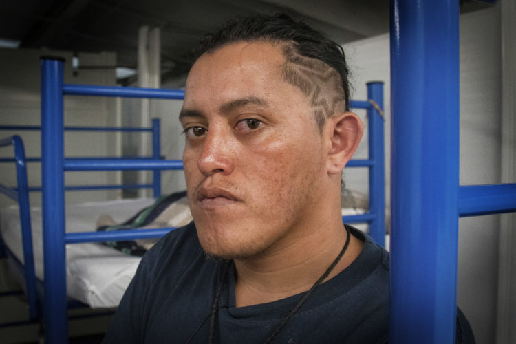 GUADALAJARA, MEXICO   07/13/2017  Mario, a migrant from Honduras, has the stars and stripes from the national Honduran flag shaved into his hair. He had been staying in the FM4 Paso Libre shelter in Guadalajara, and now he's preparing to leave FM4 to continue on the journey to the U.S. border.  After leaving FM4 at night, the men walked along the railroad tracks to a position where they can jump on board La Bestia, the moving freight train known as The Beast.