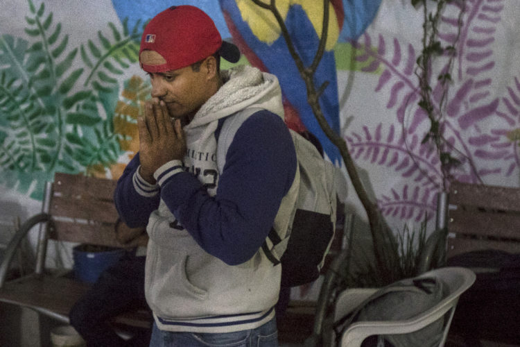 GUADALAJARA, MEXICO  07-13-2017: A Honduran migrant makes a silent prayer before departing the FM4 Paso Libre migrant shelter in Guadalajara, continuing on the hazardous journey from Central America to the U.S. border aboard the freight train known as The Beast. Here they have a chance to rest, wash and eat, while volunteers from non-governmental organizations offer a place to sleep, clean clothes, medical attention, and legal and psychological counseling.