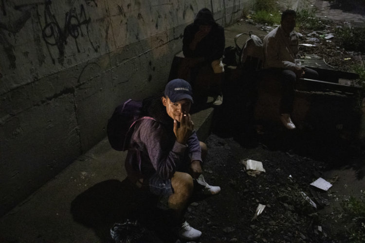 GUADALAJARA, MEXICO   07/13/2017  A group of Honduran men take a break along the railroad tracks in Guadalajara, where wild dogs and gang members lurk in the shadows, as they continue on the journey to the U.S. border. After leaving the nearby FM4 shelter, the men walked along the railroad tracks to a position where they wait to jump on board La Bestia, the moving freight train known as The Beast. According to the Migration Policy Institute (MPI), a half a million Central American immigrants ride atop La Bestia during their long and perilous journey through Mexico to the U.S. The migrants often must latch onto the moving freights, which run along multiple lines, carry products north for export, and must ride atop the moving trains, facing physical dangers that range from amputation to death if they fall or are pushed. Beyond the dangers of the trains themselves, Central American migrants are subject to extortion and violence at the hands of the gangs and organized-crime groups that control the routes north.The migrant shelter provides a clean and safe place for migrants to rest, wash and eat, while volunteers from non-governmental organizations offer clean clothes, medical attention, and free legal and psychological counseling. M4 Paso Libre was started by a group of students in 2007 and opened its first kitchen and day shelter in 2010. The nonprofit is a member of the Office of the United Nations High Commissioner for Refugees (UNHCR), assists approximately 8,000 migrants each year, and relies on regular donations and hundreds of volunteers to support the migrants who pass through.
