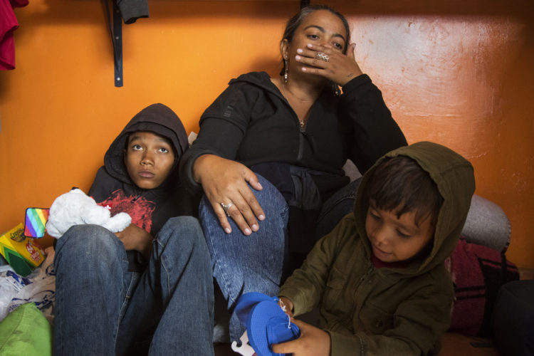 TIJUANA, MEXICO  03-09-2019: Isabela Murillo, with her sons Jose, 14, and Mateo, 3, of Honduras, sit on the floor of a cafe in Tijuana that offers free food to migrants. Along with her other son Patric, not pictured, they just arrived at the border after traveling for two months in a migrant caravan from Central America. The Border Angels volunteers brought them clean clothes, shoes, and hygiene products then helped them get to the nearby shelter, where they would spend the night before trying to apply for asylum in the U.S.
