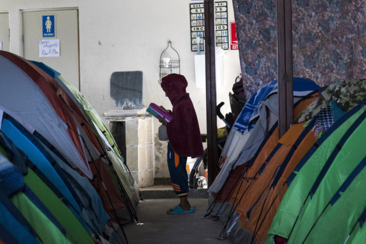 TIJUANA, MEXICO  03/09/2019: Young boy reads from a book at the migrant shelter Movimiento Juventud 2000. The shelter houses about 150 migrants, mostly families, who sleep in camping tents on a concrete floor, crammed together side by side. The shelter has been housing migrants, mainly Central Americans, since mid-2017. The Border Angels volunteers brought to the shelter clean clothes, under garments, socks, and hygiene products. All the shelters in Tijuana are overcrowded, and undersupplied. Most plan to wait in Tijuana until they are assigned a court date for their  asylum petitions  plan to put their names on the informal waiting list for U.S. Others will cross the border illegally.