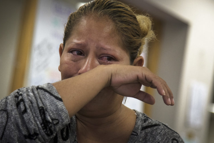 SAN DIEGO, CA  03/11/2019: A woman (unidentified) from Central America wipes away some tears while speaking with her attorney Luis Gonzalez, a HIAS Border Fellow who took on her case pro-bono. The single mother arrived in Tijuana with a migrant caravan in late February 2019, after a two month journey. She is seeking asylum in the U.S. for herself and children, after they were victims of gang violence and sexual assault at home.