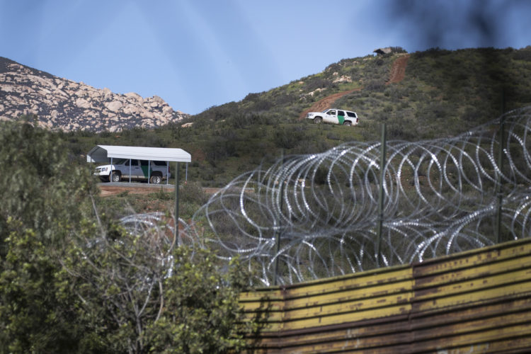 TECATE, CA  03/12/2019: CBP vehicles are parked in high vantage points above the border wall and barbed wire on the U.S. side of the border in Tecate, 40 miles east of San Diego. Tecate is a city split between the U.S. and Mexico of the same name.