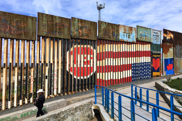 "TIJUANA, MEXICO  03/09/2019 A musician carrying a guitar walks along the border wall with an upside down U.S. flag painted with the word ""Lies"" next to it, near the beach in La Playa, Tijuana. 