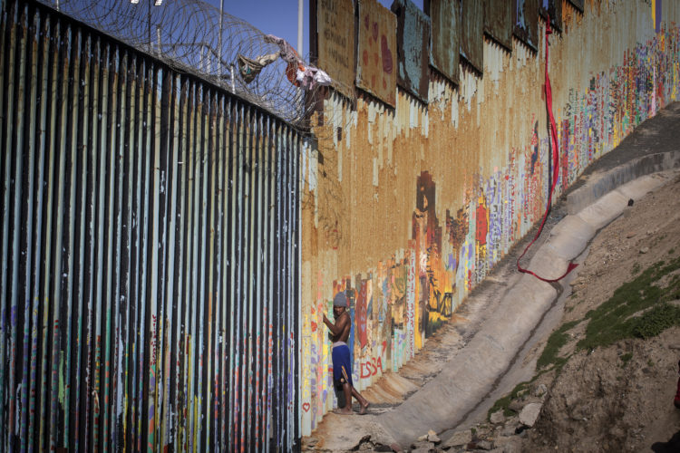 TIJUANA, MEXICO 03/12/2019: The Tijuana side of the border wall in La Playa, Tijuana is a common place for migrants to hang out. The U.S.-Mexico border is 1,933 miles long, stretching from the Pacific Ocean to the Gulf of Mexico, roughly 700 of those miles have fencing currently in place. Americans are not permitted to walk up to the border wall on the U.S side, and the area is under constant watch by the Customs and Border Patrol police. (CBP)
