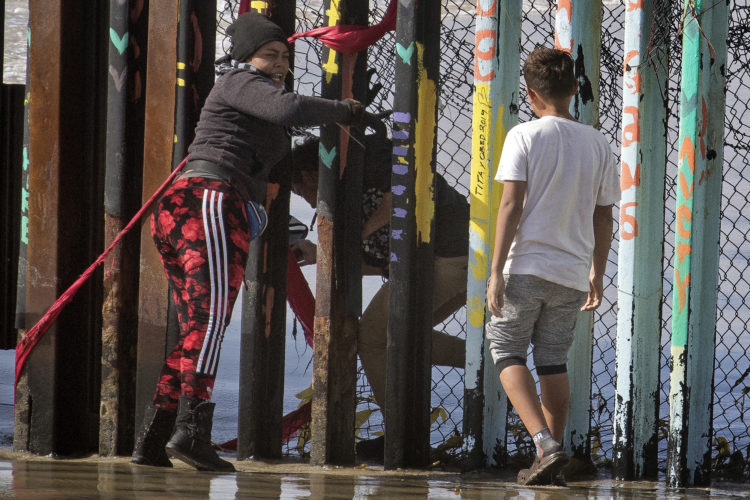 TIJUANA, MEXICO  03-13-2019: A 22-year old Honduran man carries his young child in his arms as he squeezes through the pillars and fencing on the beach in La Playa at the border wall in Tijuana with the help of a woman pushing the fence open. He then sprinted down the beach on the U.S. side of the border carrying the young child on his shoulders, while the Customs & Border Patrol (CBP) was seemingly not watching. It was later confirmed that he was not captured, and is currently living with family elsewhere in the U.S.