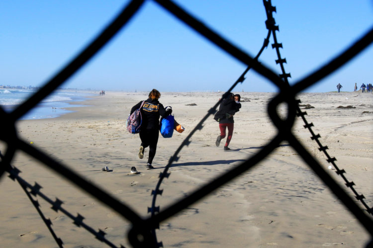 TIJUANA, MX   03/14/2019: Two migrant women, one carrying a young child, sprint down the beach carrying their belongings run down the beach heading north into the United States, after a group of migrants pushed through an opening in the border fence on the beach running past a CBP agent and ran north along the beach into the United States. They were later captured by United CBP agents, who said they arrested about 52 migrants, including 23 men, between the ages of 18 to 53, 12 women aged 21 to 50, and 17 minors between the ages of 1 and 14 years old. They were mostly from Honduras and came to Tijuana in a caravan. As they broke through the fence and ran down the beach, some dropped clothes and shoes from the backpacks, as some people on the Mexico side cheered them on.