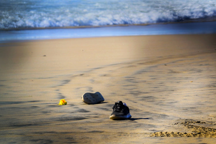 TIJUANA, MEXICO  03-14-2019:  Sneakers and a toy are left behind in the surf after a group of migrants squeezed through an opening in the border fence on the beach running past a CBP agent and ran north along the beach into the United States. They were later captured by United CBP agents, who said they arrested about 52 migrants, including 23 men, between the ages of 18 to 53, 12 women aged 21 to 50, and 17 minors between the ages of 1 and 14 years old. They were mostly from Honduras and came to Tijuana in a caravan. As they broke through the fence and ran down the beach, some dropped clothes and shoes from the backpacks, as some people on the Mexico side cheered them on.