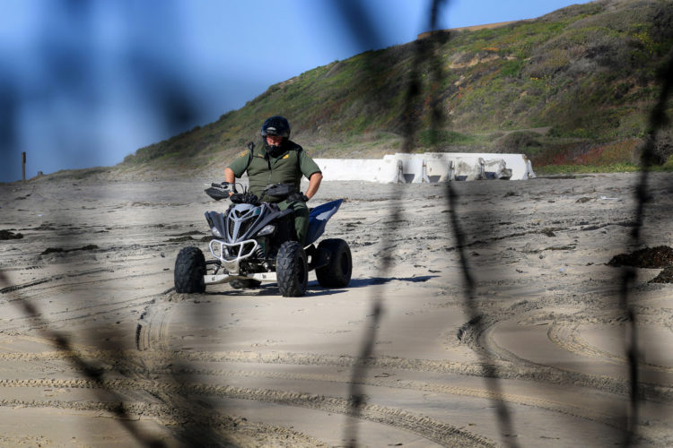 SAN DIEGO, CA- TIJUANA, MX   03-14-2019 U.S.-MEXICO BORDER WALL HONDURAN MIGRANTS BREAK THROUGH BORDER WALL:   A Custom Border Patrol Agent watches the wall on a 4x4 after a group of roughly 20-30 migrants squeezed through an opening in the border fence on the beach on La Playa Tijuana today, running past border patrol heading towards SanDiego.