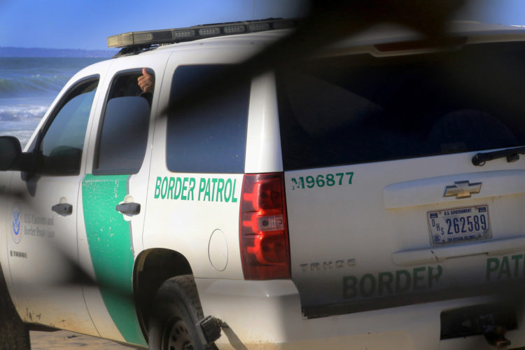 TIJUANA, MX   03/14/2019: A captured migrant gives a thumbs-up sign from the back seat of a CBP SUV after a group of migrants squeezed through an opening in the border fence on the beach running past a CBP agent and ran north along the beach into the United States. They were later captured by United CBP agents, who said they arrested about 52 migrants, including 23 men, between the ages of 18 to 53, 12 women aged 21 to 50, and 17 minors between the ages of 1 and 14 years old. They were mostly from Honduras and came to Tijuana in a caravan. As they broke through the fence and ran down the beach, some dropped clothes and shoes from the backpacks, as some people on the Mexico side cheered them on.