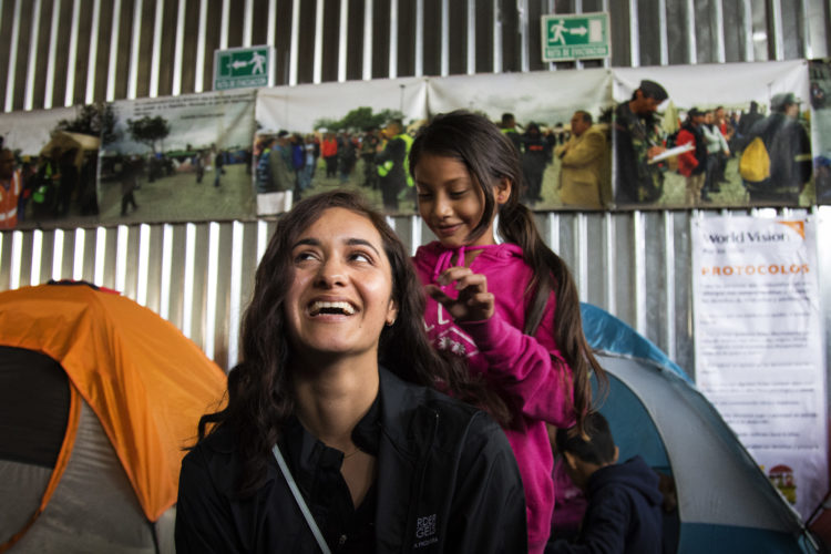 TIJUANA, MEXICO  03/09/2019: Border Angels volunteer Destany Zavala lets one of the young girls (name withheld) playfully brush her long hair at the Tijuana migrant shelter Movimiento Juventud 2000. The shelter houses about 150 migrants, mostly families, who sleep in camping tents on a concrete floor, crammed together side by side. The shelter has been housing migrants, mainly Central Americans, since mid-2017. The Border Angels volunteers brought to the shelter clean clothes, under garments, socks, and hygiene products. All the shelters in Tijuana are overcrowded, and undersupplied. Most plan to wait in Tijuana until they are assigned a court date for their  asylum petitions  plan to put their names on the informal waiting list for U.S. Others will cross the border illegally.