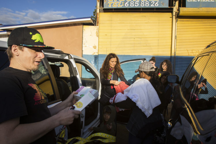 TIJUANA, MEXICO  03-09-2019: Border Angels volunteers give Isabela Murillo and her three young boys supplies after the single mother just arrived at the border after traveling for two months in a migrant caravan from Honduras. The Border Angels volunteers brought them clean clothes, shoes, and hygiene products then directed them to the nearby shelter, where they would spend the night before trying to apply for asylum in the U.S.