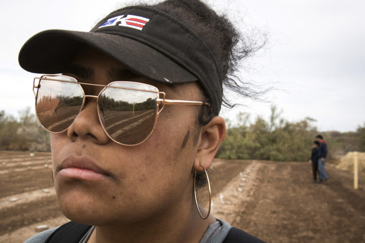 "HOLTVILLE, CA 03/10/2019:  University of Utah student Joy Kavapalu looks at the rows of unmarked graves at the ""Cemetery of the Forgotten"" where the remains of hundreds of unidentified immigrants are buried in a dirt lot behind the Terrace Park Cemetery in Holtville, CA. The unidentified migrants died in the Imperial Valley desert or mountains are buried in anonymity, an extreme reflection of the often desperate attempts by people to enter the U.S. where the flow of unauthorized immigrants has been a source of debate for decades. Hugo Castro and a group students from the University of Utah, who were on a tour of the cemetery and were volunteering for the Border Angels organization, fixed crosses that had fallen over, took photos, and said a group prayer."