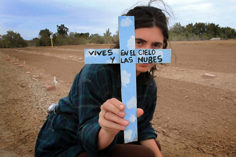 "HOLTVILLE, CA 03/10/2019:  Border Angels volunteer Amba Guerguerian holds a wooden cross that reads ""vives en el cielo y las nubes,"" or ""live in heaven and clouds"" at the ""Cemetery of the Forgotten."" She placed the cross next to an unmarked grave after it blew over in the wind.  The ""Cemetery of the Forgotten"" is where the remains of hundreds of unidentified immigrants are buried in a dirt lot behind the Terrace Park Cemetery in Holtville, CA. The unidentified migrants died in the Imperial Valley desert or mountains are buried in anonymity, an extreme reflection of the often desperate attempts by people to enter the U.S. where the flow of unauthorized immigrants has been a source of debate for decades. Hugo Castro and a group students from the University of Utah, who were on a tour of the cemetery and were volunteering for the Border Angels organization, fixed crosses that had fallen over, took photos, and said a group prayer."
