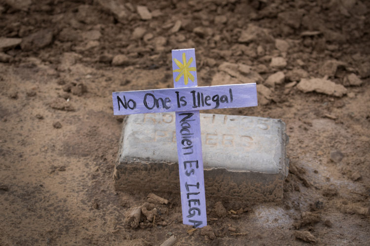 "TIJUANA, MEXICO  03-10-2019: ""No one is illegal"" says a message on one of the wooden crosses at the ""Cemetery of the Forgotten"" where the remains of hundreds of unidentified immigrants are buried in a dirt lot behind the Terrace Park Cemetery in Holtville, CA. The unidentified migrants died in the Imperial Valley desert or mountains are buried in anonymity, an extreme reflection of the often desperate attempts by people to enter the U.S. where the flow of unauthorized immigrants has been a source of debate for decades. Hugo Castro and a group students from the University of Utah, who were on a tour of the cemetery and were volunteering for the Border Angels organization, fixed crosses that had fallen over, took photos, and said a group prayer."