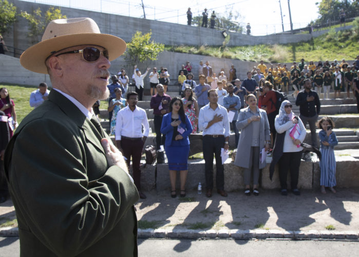 PATERSON, NJ  10-02-2019 NATURALIZATION CEREMONY AT GREAT FALLS:  Darren Boch, Superintendent of the Paterson Great Falls National Historical Park, places his hand over his heart during the playing of God Bless America. The Paterson Great Falls National Historical Park (NPS), in partnership with U.S. Citizenship and Immigration Services (USCIS), held a naturalization ceremony in the park's new amphitheater where 40 new citizens, mostly residents of Paterson, took the Oath of Allegiance to the United States.