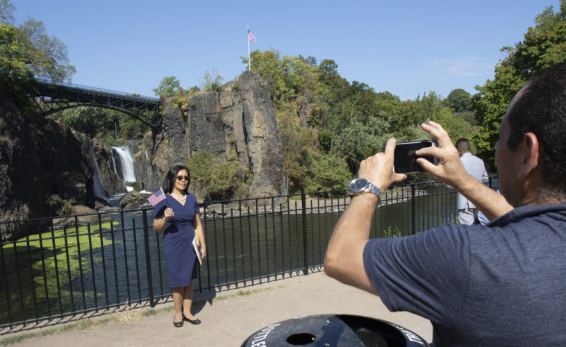 PATERSON, NJ  10-02-2019 NATURALIZATION CEREMONY AT GREAT FALLS:  Marlin Geron Rivas waves the U.S, flag while having her photo taken by the Great Falls, after taking the Oath of Allegiance to the United States. She is from the Philippines. The Paterson Great Falls National Historical Park (NPS), in partnership with U.S. Citizenship and Immigration Services (USCIS), held a naturalization ceremony in the park's new amphitheater where 40 new citizens, mostly residents of Paterson, took the Oath of Allegiance to the United States.