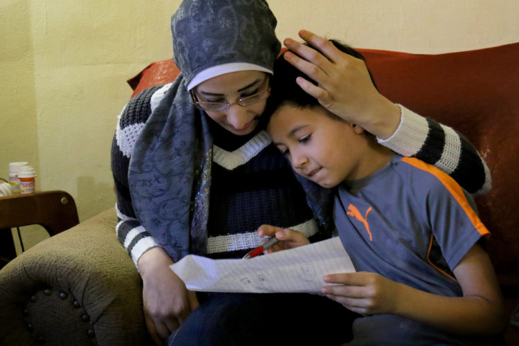 ELIZABETH, NJ   04/03/2016   SYRIAN REFUGEE FAMILIES RESETTLED IN ELIZABETH: Samer Zakkour hugs her son Mohammad, 9, as he shows her a drawing he made, in the family's apartment in Elizabeth where the IRC resettled them. The Zakkour's fled their home in Homs, Syria, after it became unsafe due to aerial bombings, They fled to Jordan where they were remained for 4-years before being resettled in Elizabeth by the IRC.