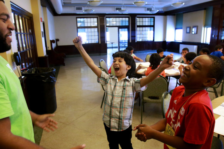 """ELIZABETH, NJ  07-26-2016: Summer Camp Director Dante Burgess plays """"rock-paper-scissors"""" with Mohammed, 9, one of the Syrian children, and Jayden, at the Gateway Family YMCA, Elizabeth Branch Summer Camp. Syrian children recently relocated to New Jersey with their families from war-torn Syria, attended a fun-filled summer camp thanks to sponsorship of two Jewish synagogues,  Bnai Keshet in Montclair and Temple Bnai Abraham in Livingston. At the camp, 16 refugee children ages 5-14 had the opportunity to play games, interact with other children and staff, and use the camp as an opportunity to improve their English and assimilate."""