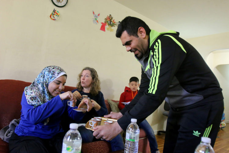 ELIZABETH, NJ   04/03/2016   SYRIAN REFUGEE FAMILIES RESETTLED IN ELIZABETH:   Mohammed Zakkour serves coffee to Kate McCaffrey of Bnai Keshet Synagogue in Montclair, and Salma Hassan, an MSU student who volunteers to tutor Syrian children and act as an interpreter, in the family's apartment in Elizabeth where the IRC resettled them. The Zakkour's fled their home in Homs, Syria, after it became unsafe due to aerial bombings.