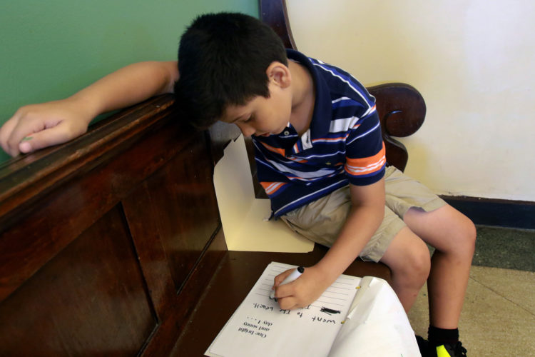 ELIZABETH, NJ  07-26-2016:  Zain, 7, one of the Syrian children writes in English in his coloring book during an arts and crafts activity at the Gateway Family YMCA, Elizabeth Branch Summer Camp. Syrian children recently relocated to New Jersey with their families from war-torn Syria, attended a fun-filled summer camp thanks to sponsorship of two Jewish synagogues,  Bnai Keshet in Montclair and Temple Bnai Abraham in Livingston. At the camp, 16 refugee children ages 5-14 had the opportunity to play games, interact with other children and staff, and use the camp as an opportunity to improve their English and assimilate.