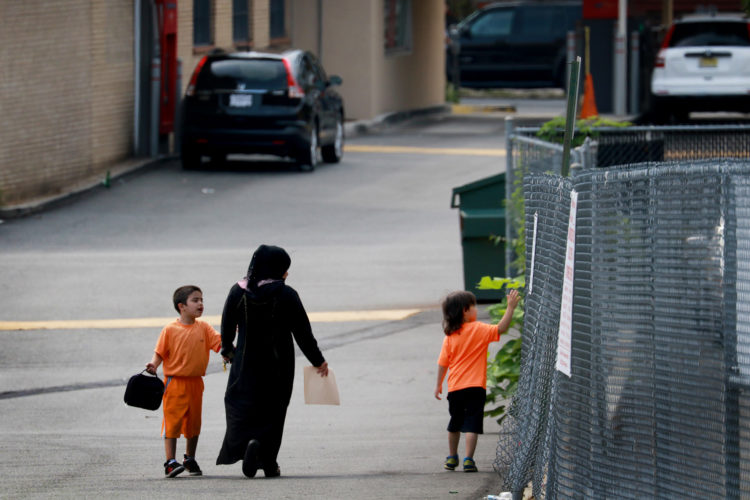 ELIZABETH, NJ  07-26-2016 SUMMER CAMP FOR SYRIAN CHILDREN:  Maryam Al Radi holds hands with her two boys at the end of the day after leaving the Elizabeth YMCA. 16 Syrian children recently relocated to New Jersey with their families from their war torn homeland,  attended a fun-filled summer camp thanks to the generosity of two North Jersey Jewish synagogues,  Bnai Keshet in Montclair and Temple Bnai Abraham in Livingston,  and the Elizabeth YMCA. At the camp the 16 refugee children had the opportunity to play outdoor and indoor games, interact with other children, and improve their English. The children ages 5-14, were able to take respite from the summer heat, after the groups teamed up to raise the necessary funds for the two-week recreation and educational program.