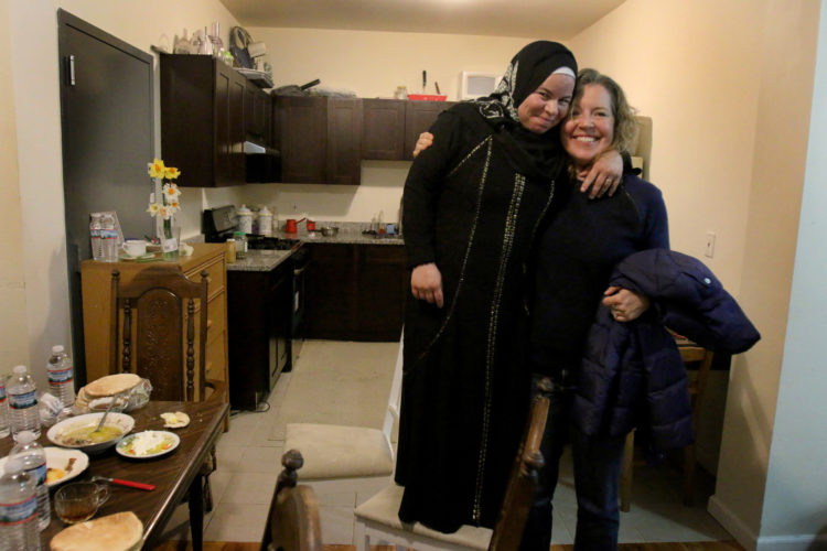 """ELIZABETH, NJ   04/03/2016   SYRIAN REFUGEE FAMILIES RESETTLED IN ELIZABETH:   Maryam Al Radi jokingly stands on a chair because she is short, as she hugs her new friend Kate McCaffrey  from Bnai Keshet Synagogue. Bnai Keshet has """"adopted"""" the AL Radi's, providing friendship and assistance in helping the family get acclimated to their new life in the US."""