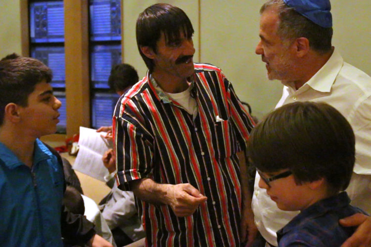 MONTCLAIR, NJ   04/23/2016   SYRIAN REFUGEE FAMILIES RESETTLED IN ELIZABETH/ COMMUNITY SEDER:  Lee Siegel and his son Julian, 9, of the Bnai Keshet Synagogue welcome Fadel Al Radi and his son Mohammed age 13. The Bnai Keshet congregation invited the Al Radi family, who are Muslim, to their community Seder for Passover. The Bnai Keshet congregation of Montclair has informally adopted the Al Radi family, who are Syrian refugees recently relocated in Elizabeth last year. They fled their home in Daraa, Syria, after it was badly damaged by aerial bombings in which wife Maryam was injured. After their son Mohammed, 7, became ill, they fled to Jordan where they were remained for 3-years before being resettled in Elizabeth by the IRC, they have 4 children.