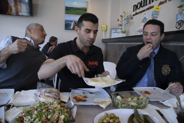 04-17-19 PATERSON, NJ:  Andre Sayegh, the mayor of Paterson, NJ, right, eats with Albert and George Noury (note their name and the restaurant name are spelled differently) who own the Nouri.Cafe on Main Street in South Paterson. Sayegh is the first Arab-American to lead the city, which has had a long-thriving Middle Eastern immigrant community in the southern district of the city known as South Paterson. Sayegh's was born to a Syrian mother and a Lebanese father, and is Christian, was a longtime city councilman and was elected mayor in 2018.