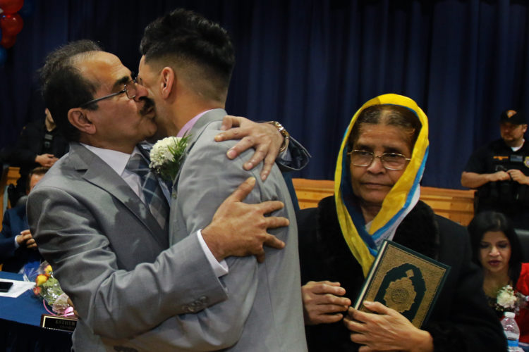 PROSPECT PARK, NJ  01-05-2019: Intashan Chowdhury embraces his father Golam after he was sworn-in as Prospect Park's new borough administrator, as his grandmother Dilara looks on at right. the 22-year old is believed to be the youngest town manager in New Jersey history, if not the nation, and is first of Bengali descent. He is a Rutgers graduate student, and was sworn-in by his long-time mentor, Mayor Mohamed T. Khairullah, a teacher of his in high school. His grandmother is the eldest relative living and is clutching the Quran for a historic occasion.