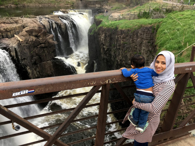 04-19-19 PATERSON, NJ:  Bangladeshi immigrant Tahira Afroz and her 12-month old son Azaan pose for a photo on the walkway over the Great Falls in downtown Paterson, NJ. This was the first time they visited the iconic symbol of the industrial city. The falls of the Passaic River is a prominent waterfall, 77 feet high, on the Passaic River in the city of Paterson in Passaic County, New Jersey, United States. The falls and surrounding area are protected as part of the Paterson Great Falls National Historical Park, administered by the National Park Service.