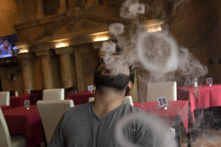 04-14-19 PATERSON, NJ:  Danny Usmani, 26, blows smoke rings as he enjoys a hookah at Darna in South Paterson. Darna serves Lebanese and Mediterranean food in a large space that can seat around 300, and features  a waterfalls and a terra-cotta replica of that famed architectural site in Jordan, Petra, seen on the wall behind them. He is from Teaneck, NJ.