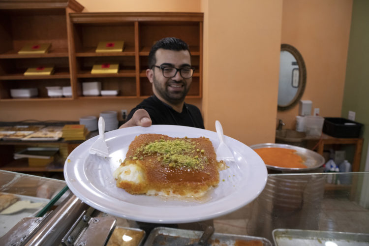 04-19-19 PATERSON, NJ: Mohammad Alsongi serves a fresh plate of Kanefeh at Al Basha Bakery on Main Street in South Paterson. Kanafeh is a popular traditional Levantine dessert made with thin noodle-like pastry, or dough soaked in sweet, sugar-based syrup, and typically layered with cheese, or with other ingredients such as clotted cream or nuts.